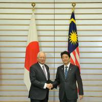 Malaysian Prime Minister Najib Razak  and Prime Minister Shinzo Abe shake hands following a bilateral summit meeting in Tokyo  on Nov. 16. | MINISTRY OF FOREIGN AFFAIRS, MALAYSIA
