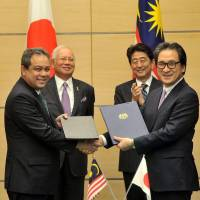 Malaysian Investment Development Authority (MIDA) CEO Azman Mahmud and Japan External Trade Organization (JETRO) Chairman Hiroyuki Ishige shake hands after signing a memorandum of cooperation in Tokyo on Nov. 16. | MIDA