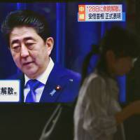 People walk past a large monitor in Tokyo on Monday showing Prime Minister Shinzo Abe announce a plan to dissolve the Lower House and call a snap election. | KYODO