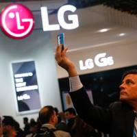 An attendee takes a photo on the LG Electronics Inc. stand on the opening day of the Mobile World Congress in Barcelona, Spain, in February. | BLOOMBERG