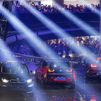 Hundreds of people watch a presentation by BMW on the opening day off the IAA car show in Frankfurt on Saturday. | AP