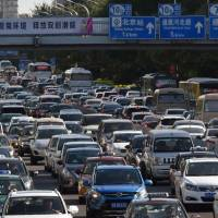 Cars clog a street in Beijing on Monday. China is gearing up to ban gasoline and diesel cars, a move that would boost electric vehicles and shake up the auto industry in the world's biggest but pollution-plagued market. | AFP-JIJI