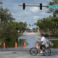 A man carrying a surf board bikes past a flooded street after Hurricane Irma made landfall in Daytona Beach, Florida, Monday. | REUTERS