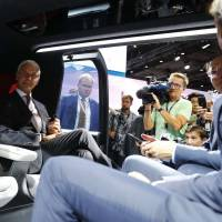 Volkswagen CEO Matthias Mueller sits in a Sedric self-driving electric vehicle during the opening of the Frankfurt auto show in Germany on Monday. | REUTERS