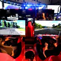 Visitors to the Sony booth try out the Gran Turismo Sport driving game at the Makuhari Messe in the city of Chiba on Thursday. | YOSHIAKI MIURA