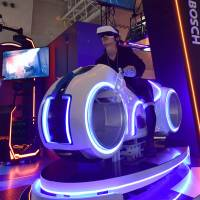 A visitor tries out a virtual reality motorcycle attraction reminiscent of 'Tron' at a preview of the Tokyo Game Show on Thursday ahead of its official opening to the public this weekend. The attraction is the creation of Tokyo-based firm JPPVR technology. | YOSHIAKI MIURA