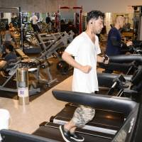 A man works out at the Ebisu, Tokyo, outlet of Anytime Fitness club on Aug. 10. | KYODO