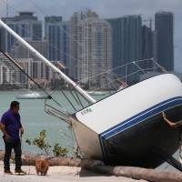 A man walks past a boat that went ashore after the passing of Hurricane Irma in Key Biscayne, Florida, Monday. | REUTERS