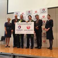 Japan Airlines President Yoshiharu Ueki (center right) and Hawaiian Airlines President and CEO Mark Dunkerley (center left) hold up a board announcing a partnership between the two carriers at a news conference in Tokyo on Tuesday. | ALEX MARTIN