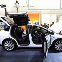 Visitors inspect a Tesla Co. Model X electric automobile, fitted with Panasonic batteries, on the Panasonic Corp. exhibition stand at the IFA Consumer electronics show in Berlin on Sept. 1. | BLOOMBERG