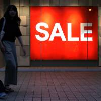 Shoppers walk past a sale sign displayed at a store in Osaka. | BLOOMBERG