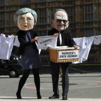 Protesters depicting media magnate Rupert Murdoch and Britain's Prime Minister Theresa May demonstrate opposite the Houses of Parliament in London Tuesday. | REUTERS