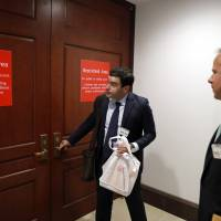 Twitter's Carlos Monje, public policy and philanthropy director, tries the door with Colin Crowell, head of global public policy, to enter a closed door meeting with the House Intelligence Committee on Capitol Hill Thursday in Washington. Officials from Twitter are on Capitol Hill as part of the House and Senate investigations into Russian interference in the 2016 election. | AP