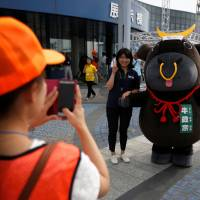 A visitor poses for a photographer with official cattle mascot Ushi-Masamune at the 11th National Japanese Beef Ability Expo in Sendai. | REUTERS