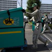 Employees of Yamato Transport Co. push carts loaded with parcels for distribution in Musashimurayama, Tokyo, in May. | BLOOMBERG
