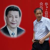 A man passes a poster of Chinese President Xi Jinping in Shanghai on Thursday.   AFP-JIJI