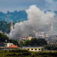 Smoke billows from buildings in Marawi on the southern Philippine island of Mindanao on Saturday during fighting between government troops and Muslim militants. | AFP-JIJI
