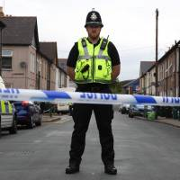 A police officer stands guard at a cordon near a house in Newport, south Wales, on Wednesday as police continue their investigations into the Sept. 15 terrorist attack on a London subway train. | AFP-JIJI