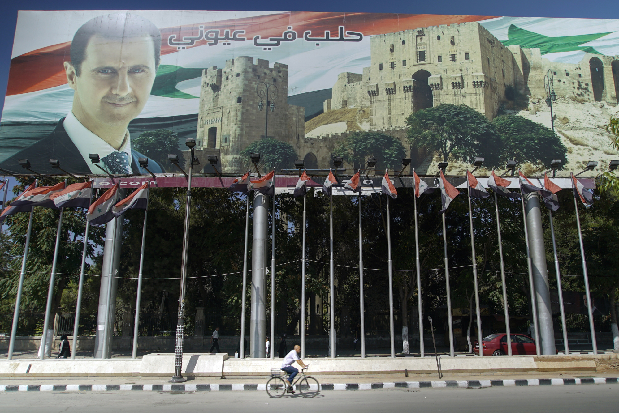 A man rides a bicycle past a billboard depicting Syrian President Bashar Assad, which reads 'Aleppo is in my eyes,' in the city on Sept. 12. | AP