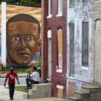 A mural depicts Freddie Gray in JUne 2016 near blighted row homes in Baltimore, at the intersection where Gray was arrested. The U.S. Department of Justice won't bring federal charges against six police officers involved in the arrest and death of Freddie Gray, a young black man whose death touched off weeks of protests and unrest in Baltimore. | AP