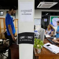 Journalists work at the newsroom of The Cambodia Daily newspaper in Phnom Penh Sunday. | REUTERS