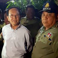 Cambodian opposition leader Kem Sokha is escorted by police at his home in Phnom Penh on Sunday. Kem Sokha was arrested early Sunday accused of treason, the government said in a statement, the latest in a flurry of legal cases lodged against critics and rivals of strongman Prime Minister Hun Sen. | AFP-JIJI