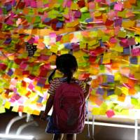 During a demonstration in Hong Kong on Aug. 2, a girl looks at messages supporting student protest leaders who have been jailed over the 2014 pro-democracy Umbrella Movement. | REUTERS