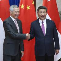 Singapore Prime Minister Lee Hsien Loong (left) shakes hands with China's President Xi Jinping on Sept. 20 before a meeting at The Great Hall Of The People in Beijing. Xi welcomed Lee to Beijing as the two sides seek to patch up relations following months of tensions over China's claims in the South China Sea and relations with the U.S. | AP