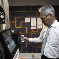 An employee using a smartphone demonstrates a bitcoin ATM at the Coin Trader bitcoin retail store at the Nakano Broadway complex in Tokyo's Nakano Ward on Wednesday. | BLOOMBERG