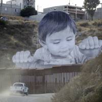 Artist's giant portrait of toddler peers over U.S.-Mexico border wall