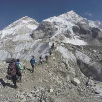 International trekkers pass through a glacier at the Mount Everest base camp Nepal in 2016. Scientists say a third of the ice stored in Asia's glaciers will be lost by the end of the century even if global warming stays below 1.5 degrees Celsius. | AP