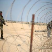 A member of the Palestinian security forces loyal to Hamas stands guard as men set up a barbed wire on the border with Egypt, in Rafah in the southern Gaza Strip, Aug. 24. | REUTERS