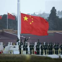 Chinese paramilitary policemen perform a flag-raising ceremony on Tiananmen Square in Beijing in this file photo. | AP