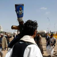 A follower of the Shiite Houthi movement holds a rifle with an image of the movement's leader, Abdul-Malik al-Houthi, during a ceremony marking Eid al-Ghadir in Sanaa Sept. 9. | REUTERS