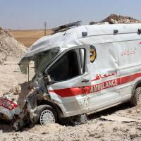 A destroyed ambulance from the Syrian Civil Defense is seen in the town of Khan Sheikun in Syria's Idlib province on Friday following reported Russian airstrikes. At least 22 civilians have been killed in 48 hours of heavy airstrikes by Syria's regime and its ally Russia in northwestern Syria. | AFP-JIJI