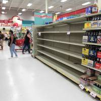Customers walk near empty shelves that are normally filled with bottles of water after Puerto Rico Gov. Ricardo Rossello declared a state of emergency in preparation for Hurricane Irma, in San Juan Monday. | REUTERS