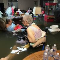 Residents of La Vita Bella nursing home in Dickinson, Texas, sit in floodwaters following the passage of Hurricane Harvey on Aug. 27. | AP