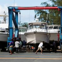Workers put boats on dry land in preparation, as Hurricane Irma, barreling toward the Caribbean and the southern United States, was upgraded to a Category 4 storm, in San Juan, Puerto Rico, Monday. | REUTERS