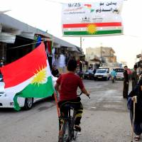 A boy rides a bicycle with the flag of Kurdistan in Tuz Khurmato, Iraq, Sunday. | REUTERS
