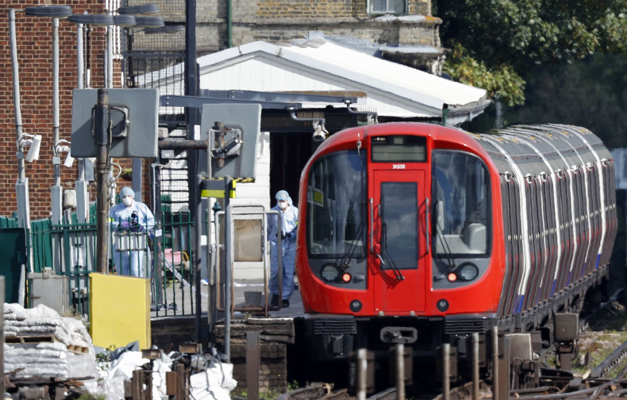 Police forensics officers examine a subway train car at Parsons Green Station in southwest London on Friday following a bomb blast on a packed train. | AFP-JIJI