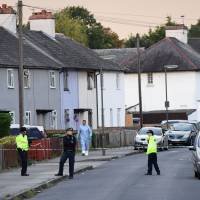 An investigator (center) leaves a house during a police raid on Saturday in Sunbury, Surrey, near London. | AFP-JIJI