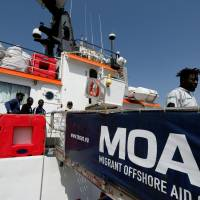 Migrants disembark from the Malta-based NGO Migrant Offshore Aid Station (MOAS) ship Phoenix after it arrived with migrants and a corpse on board, in Catania on the island of Sicily May 6. | REUTERS