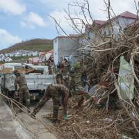 Members of the Guadeloupe Adapted Military Service Regiment gather detritus on Monday as they clean the polyvalent secondary school in Concordia on the French Caribbean island of St. Martin, after it was hit by Hurricane Irma, and in order to limit the risk of flooding and projectiles as Hurricane Maria approaches the Caribbean. | AFP-JIJI