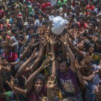 Rohingya Muslims, who crossed over from Myanmar into Bangladesh, attempt to catch a bag of rice thrown at them during distribution of aid near Balukhali refugee camp on Thursday. | AP