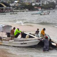 Fishermen take their boats out of the sea in anticipation of the arrival of Hurricane Max in Puerto Marquez, Guerrero state, Mexico, Thursday.   AFP-JIJI