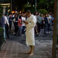 People gather on a street in downtown Mexico City during an earthquake on Thursday. The powerful 8.0 magnitude earthquake struck southern Mexico, the U.S. Geological Survey said, with seismologists warning of tsunami of more than three meters (10 feet). | AFP-JIJI