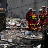 Members of Israeli (left) and Spanish rescue teams talk while standing on the rubble of a collapsed building, after an earthquake, in Mexico City Monday. | REUTERS