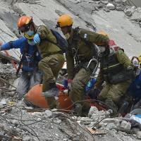 Rescuers remove the body of a man who survived the quake but died before they were able to reach him during the search for survivors at a flattened building in Mexico City on Thursday two days after a strong quake hit central Mexico. | AFP-JIJI