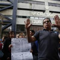 People who work inside an office of the Secretary of Public Security organize in the street as they collectively refuse to return to work inside the building, which they say suffered internal damage in last week's 7.1 magnitude earthquake in Mexico City, Monday. They are demanding independent inspectors confirm the building is safe before returning to work inside. | AP