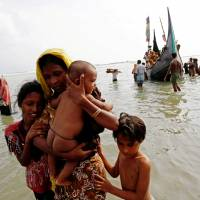 Rohingya refugees come ashore in Teknaf, Bangladesh, on Tuesday after crossing the Bay of Bengal from Myanmar. | REUTERS